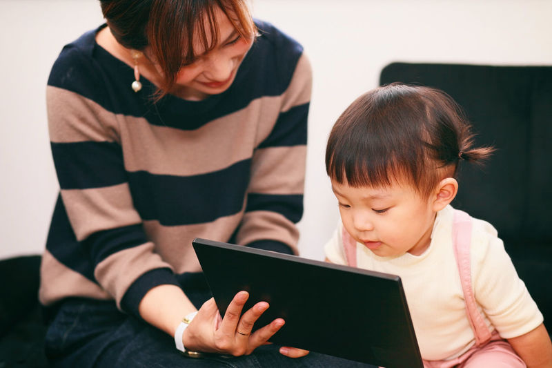 Mother with daughter using digital tablet at home