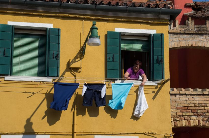Architecture Building Exterior Built Structure Burano Clothes Day Drying Full Length Italy Laundry Lifestyles One Person Outdoors Painted Houses People Real People Travel Venice Venice, Italy Window Windows