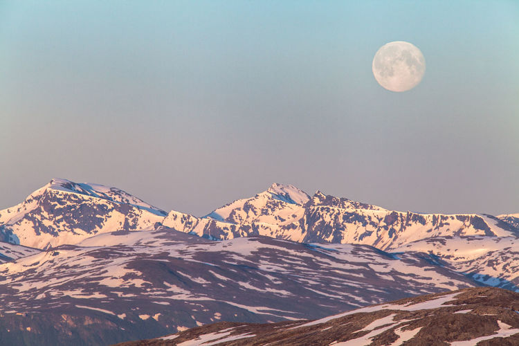 Tranquil view of snowcapped mountains against moon in sky