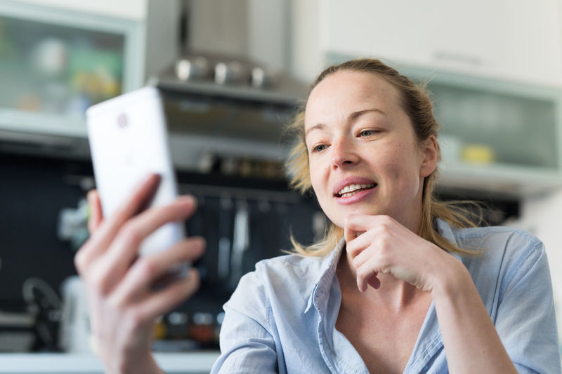 Businesswoman talking on phone working at home