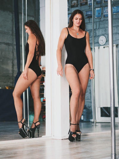 Full length of sensuous pole dancer reflecting on mirror while standing in studio