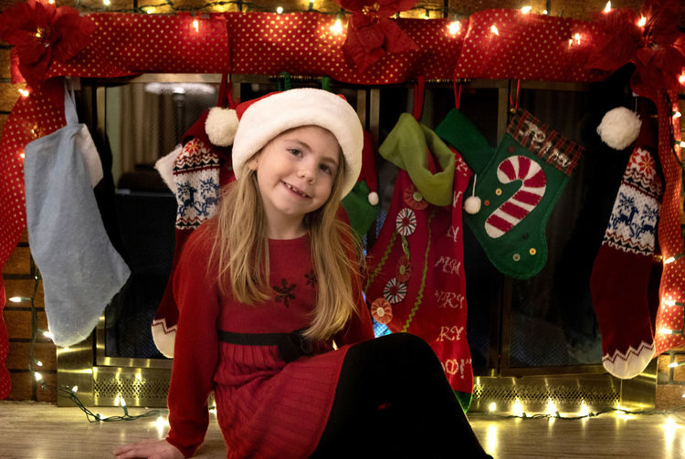 Portrait of girl smiling while sitting against christmas stockings at home