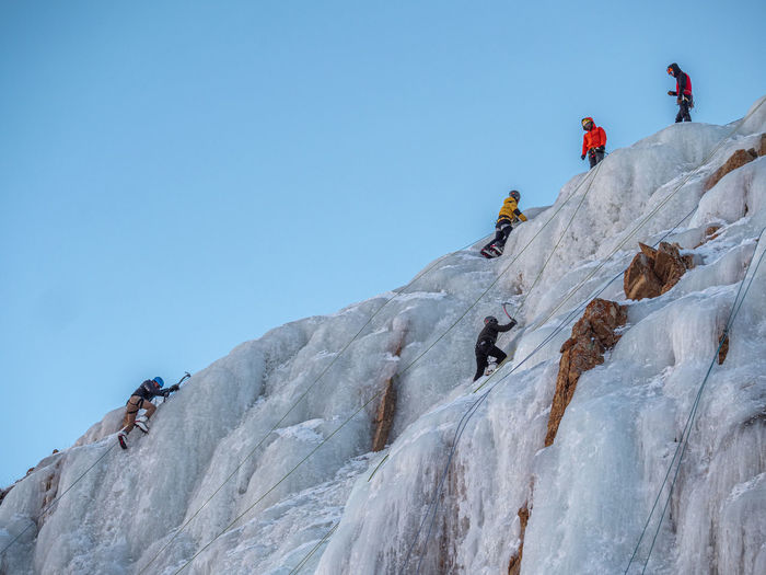 Low angle view of people on mountain against clear sky