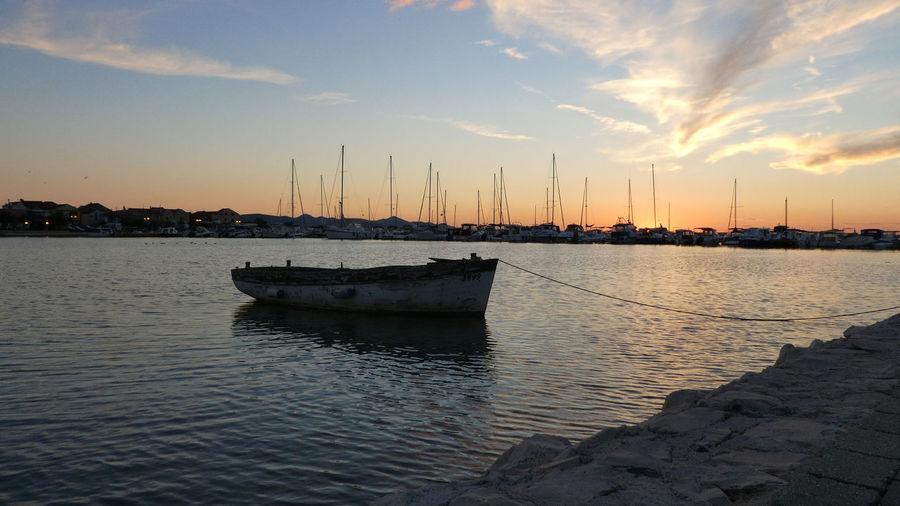 Sailboats moored in sea at sunset