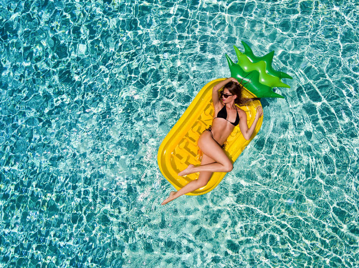 Beautiful, blonde woman enjoys the summer sun on a pineapple shaped pool float Blonde Modern Pineapple Beautiful Woman Bikini Day Floating Floating On Water High Angle View Holiday Inflatable  Leisure Activity Lying Down Ocean One Person Outdoors Pool Pool Raft Sexygirl Summer Sunlight Swimming Pool Turquoise Vacations Water