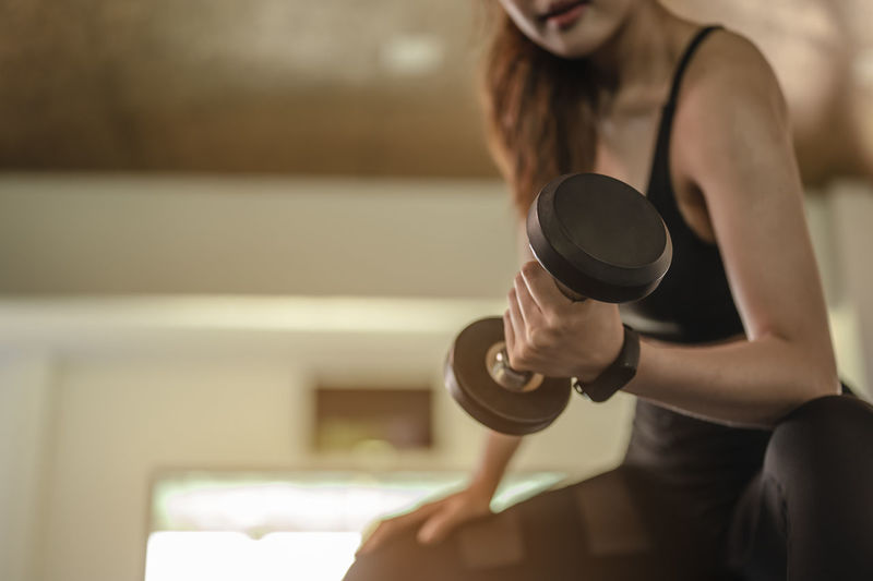 Low angle view of woman lifting dumbbell in gym