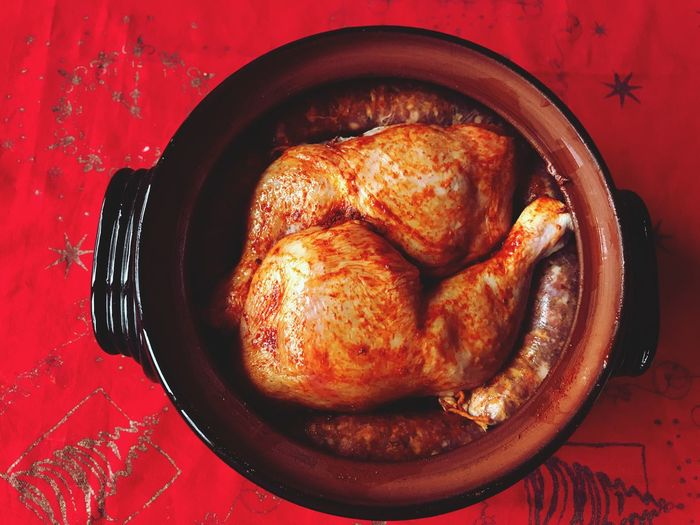 Directly above shot of roasted chicken in container on red tablecloth