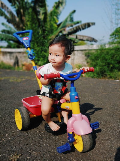 Cute boy riding toy car on land