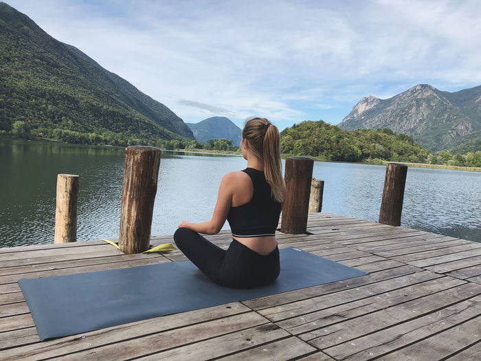 Rear view of woman sitting by lake against mountains