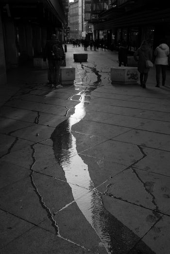People walking on wet footpath in city