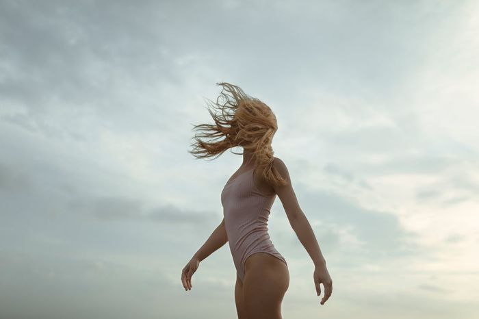 FULL LENGTH OF WOMAN WITH PALM TREE AGAINST SKY