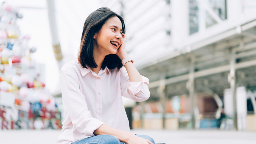 Portrait of young woman happy and smiling. One Person Young Adult Focus On Foreground Happiness Smiling Emotion Front View Architecture Young Women Lifestyles Leisure Activity Sitting Three Quarter Length Casual Clothing Real People Women Looking Away Day Hair Beautiful Woman Hairstyle Outdoors Contemplation