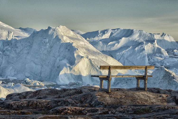 View on the Sermeq Kujalleq glacier in the midnight sun, rocks with wooden bench, Greenland. Sermeq Kujalleq Sermeq Kujalleq Grönland Greenland Ilulissat Midnight Sun Beauty In Nature Cold Temperature Glacier Glaciers Ice Landscape Mountain Nature No People Rock Scenics - Nature Sky Snow Snowcapped Mountain Tranquil Scene Winter Snowcapped Cold Frozen Frost Snow Covered Arctic Glacial
