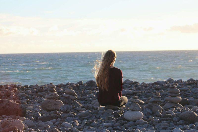 Woman sitting on rocks at beach against sky