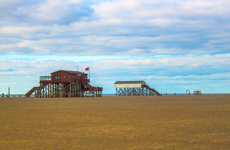 Lifeguard hut on beach against cloudy sky