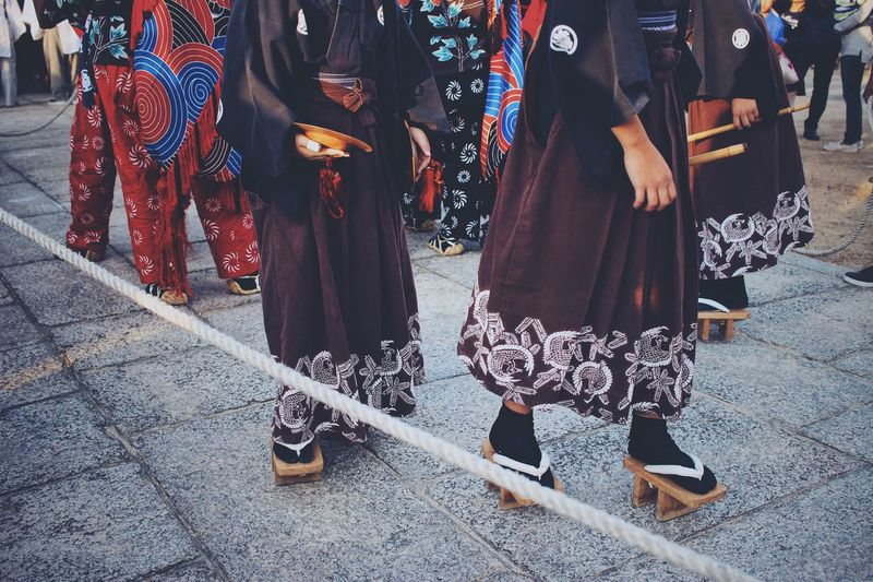 Low section of women in traditional clothing walking on street