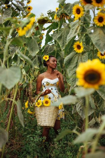 Flower child Plant Flower Flowering Plant One Person Front View Growth The Portraitist - 2018 EyeEm Awards Yellow Real People Young Adult Casual Clothing Standing Young Women Freshness Outdoors Lifestyles Leisure Activity Women Beauty In Nature Nature Day