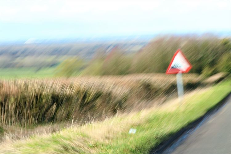 Uphill Struggle 10% Incline Driving Blurred Motion Close-up Day Field Grass Motion Nature No People Outdoors Road Road Sign Rural Scene Sky Speed Uphill Warning Triangle