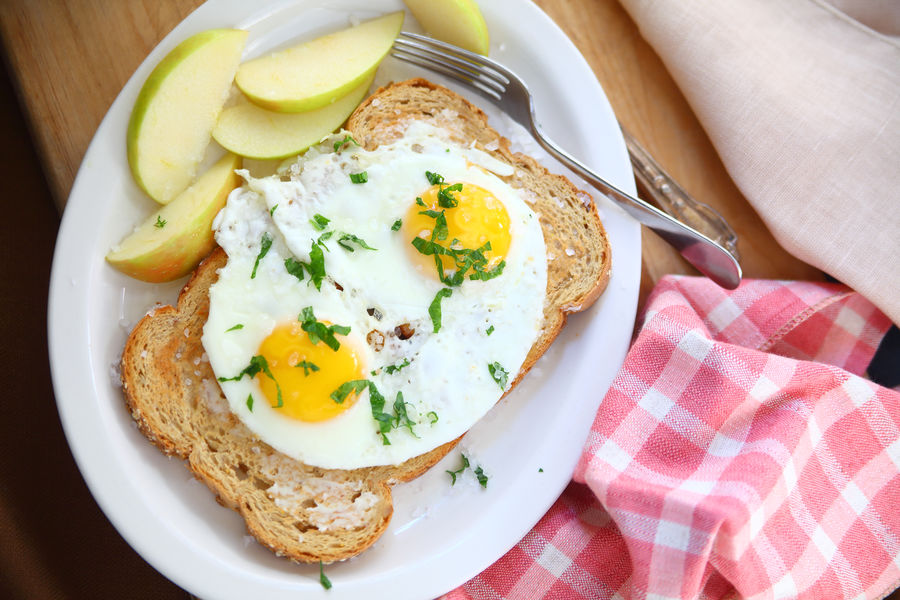 Fried eggs on toast breakfast with apples American Food Apple Slices Bread Breakfast Close-up Day Dish Towel Fabric Food And Drink Fork Fried Eggs Garnished With Cilantro Indoors  Muted Colors Napkin No People Overhead Pattern Platter Ready-to-eat Textures Toasted Bread