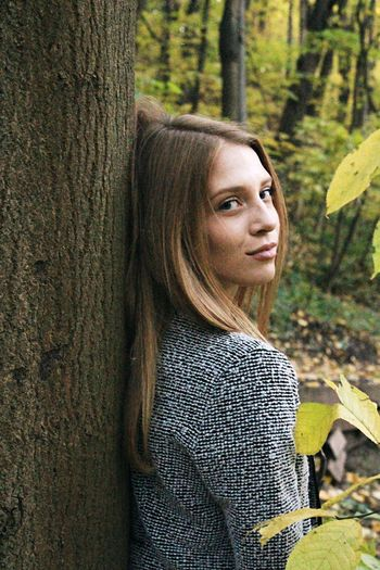 Portrait of woman against tree trunk in forest