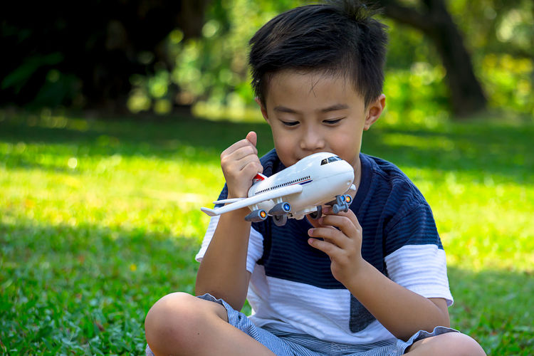 A boy playing with airplane dreams of pilot aviator traveling in nature park background Beauty In Nature Boys Casual Clothing Child Childhood Day Elementary Age Grass Holding Leisure Activity Lifestyles Model Airplane Nature One Person Outdoors Park - Man Made Space People Playing Real People Sitting Tree