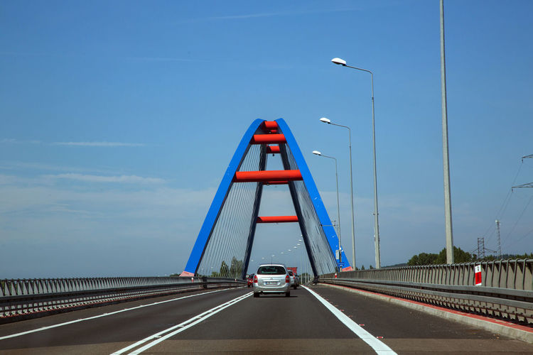 Architecture Blue Bridge Bridge - Man Made Structure Built Structure Car Connection Diminishing Perspective Direction Land Vehicle Mode Of Transportation Motion Motor Vehicle Multiple Lane Highway No People Outdoors Road Road Marking Sign Sky Symbol The Way Forward Transportation