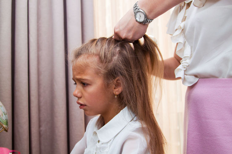 Midsection of mother tying daughter hair