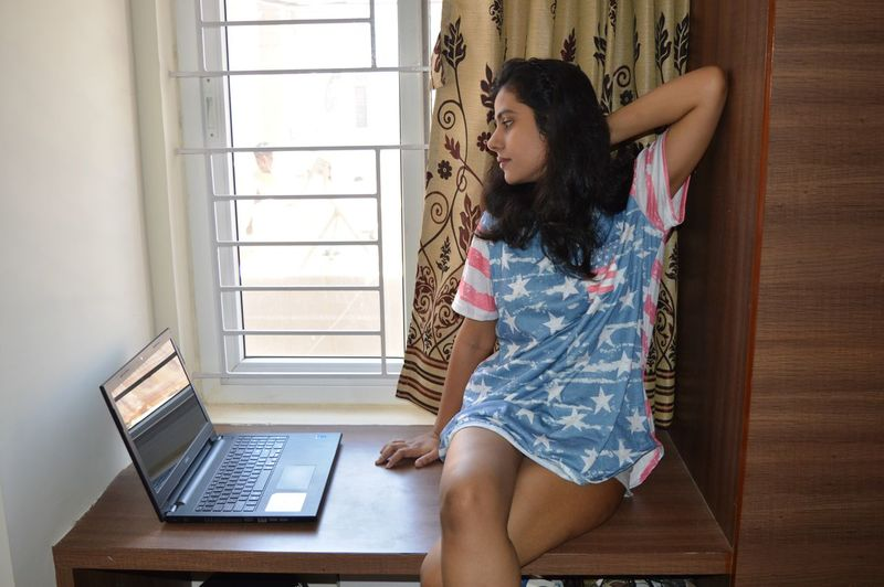 Young woman with laptop on table sitting at home