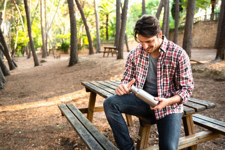 Full length of man sitting on bench in park