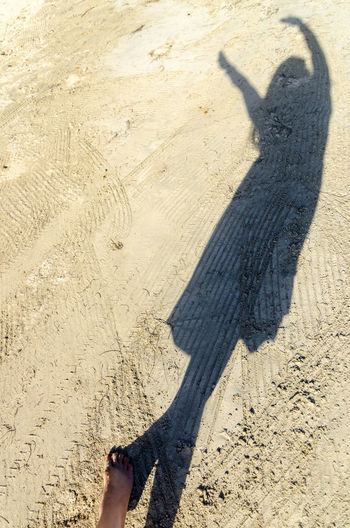Shadow Of Woman On Sand During Sunny Day