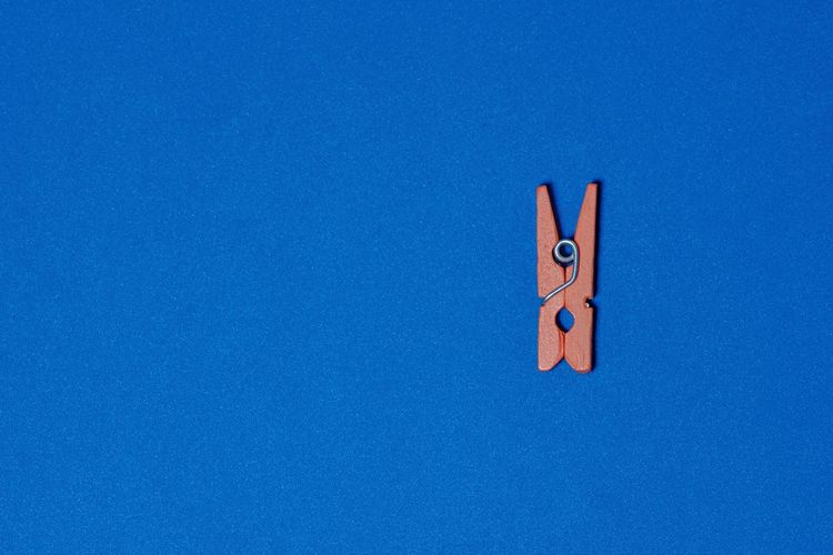 Low angle view of clothespins on blue sky