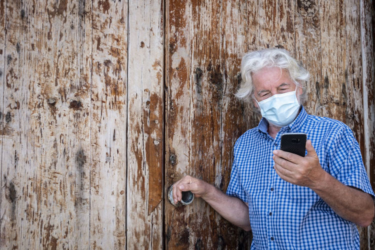 Midsection of man using mobile phone outdoors