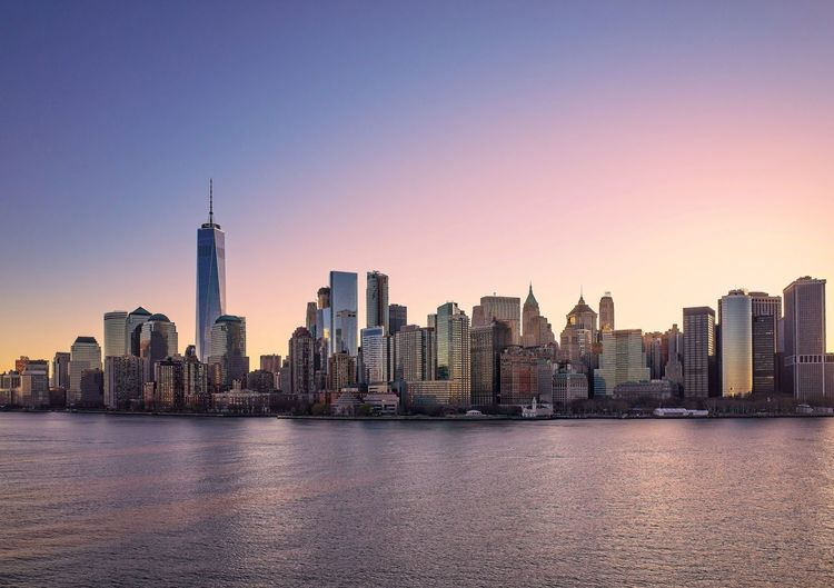 Manhattan skyline and one world trade center at sunrise.