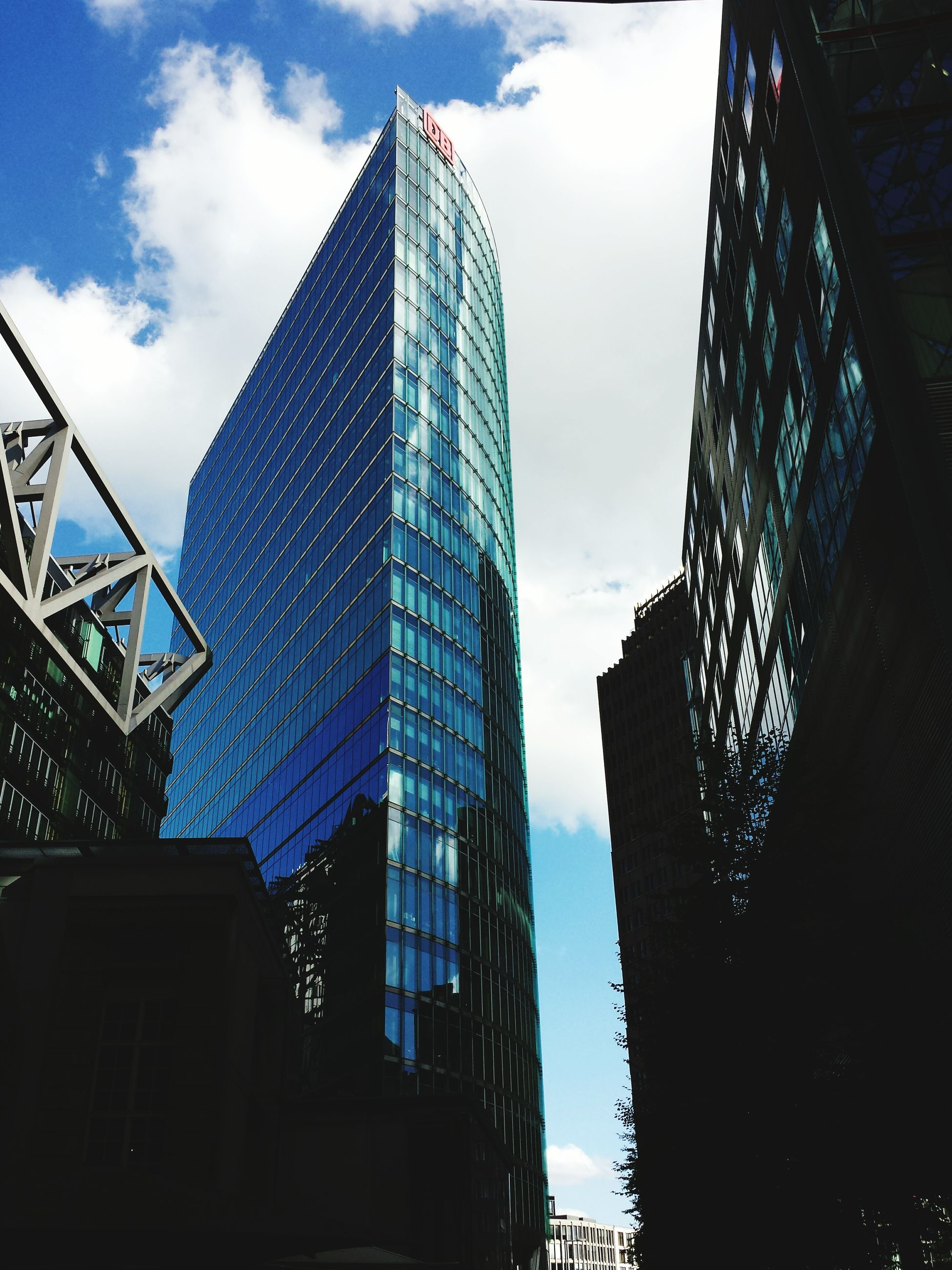 architecture, built structure, building exterior, skyscraper, low angle view, tall - high, modern, tower, city, office building, sky, capital cities, glass - material, tall, travel destinations, cloud - sky, famous place, reflection, development, international landmark