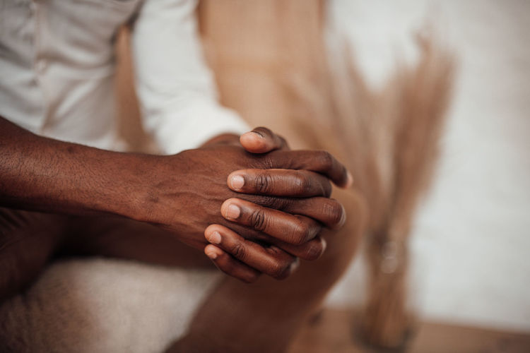 Close-up of man holding hands over blurred background