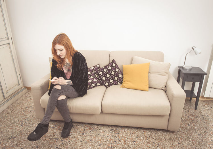 Young redhead woman at home on a sofa texting with mobile phone Alternative Girls Casual Clothing Front View Ginger Woman Home Interior Indoors  Leisure Activity Lifestyles Mobile Phone Person Piercing Redhead Relaxation Sitting Sofa Tattooed Texting Young Adult Young Women