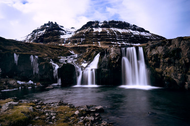 LOW ANGLE VIEW OF WATERFALL IN ICELAND