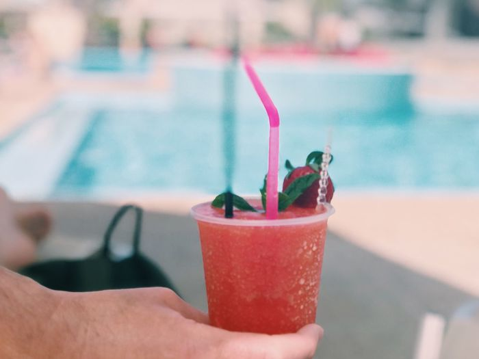 Cropped image of hand holding drink against swimming pool