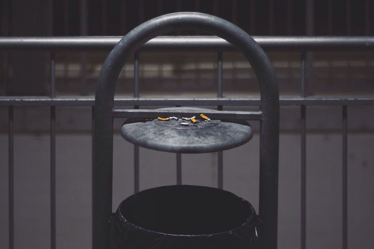 Burnt cigarettes on railing