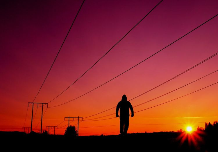 Silhouette man walking against electricity pylon during sunset