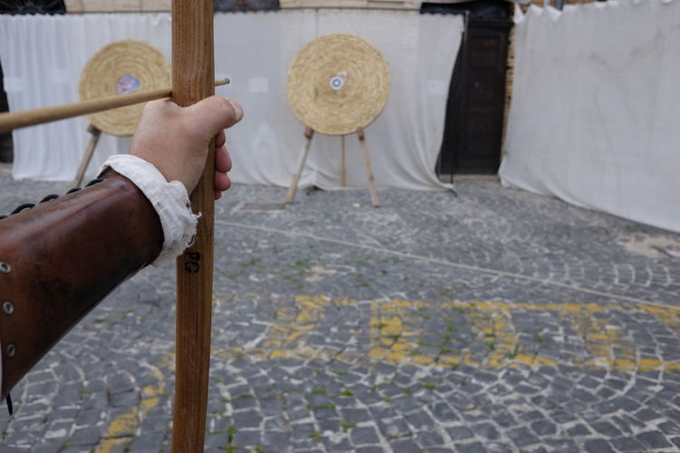 Cropped Hand Of Archer Aiming At Target
