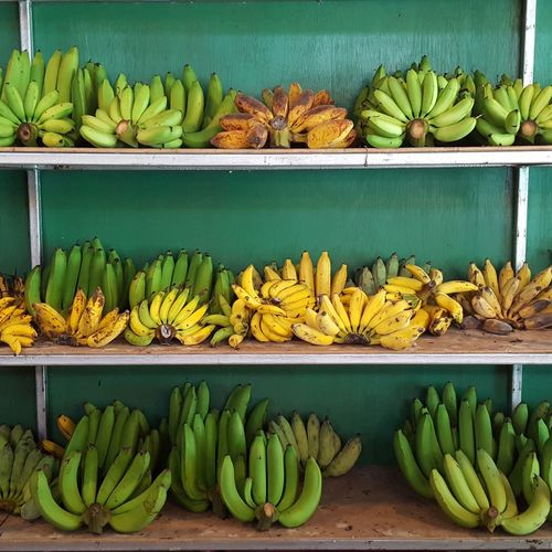 Bananas on wooden shelf for sale at market