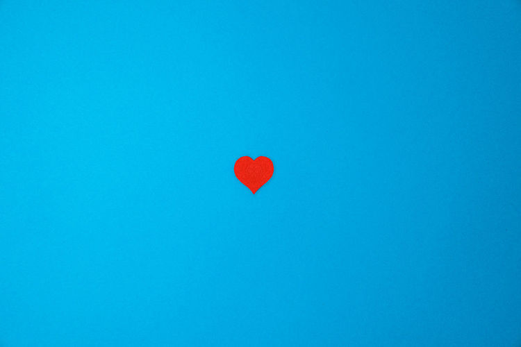 Low angle view of heart shape balloon against blue sky