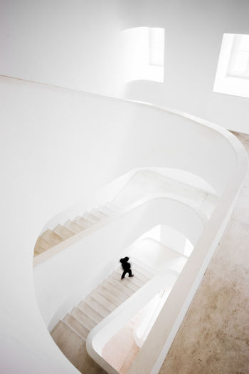Bright white stairway with a person moving in Lisbon, Portugal. Indoors  Architecture One Person Staircase Steps And Staircases High Angle View Walking Men White Color Modern Lifestyles Built Structure Railing Flooring Day Simplicity Home Interior Sunlight Business Person Interior Stairway person White Bright