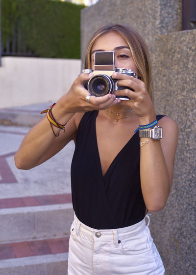 Young woman photographing camera