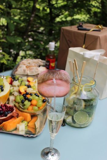 High Angle View Of Fresh Fruits And Champagne On Table In Back Yard