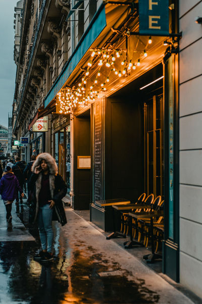 Adult Architecture Building Exterior Built Structure City City Life Dusk Footpath Group Of People Illuminated Incidental People Night Outdoors People Rain Real People Store Street Walking Wet Women