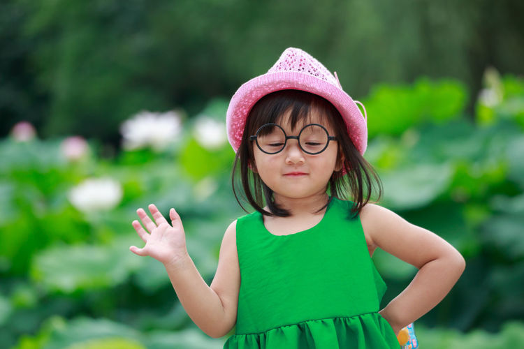 Close-Up Of Girl Standing Against Plants