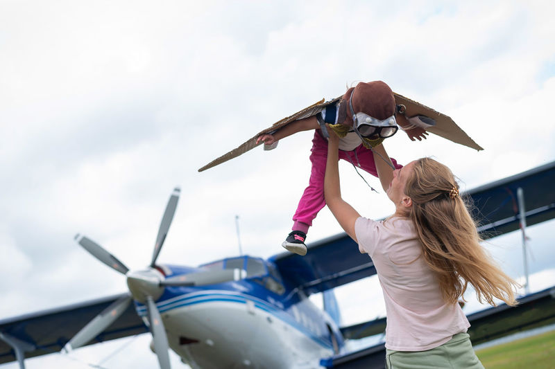 Low angle view of woman holding airplane against sky