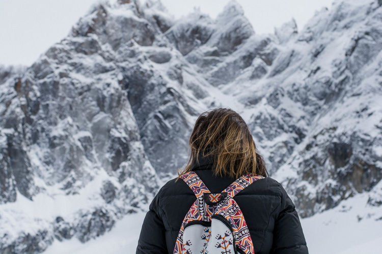 Low angle view of woman standing against snowcapped mountains